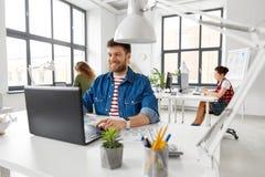 Uśmiechnięty kreatywnie mężczyzna z laptopem pracuje przy biurem obrazy stock