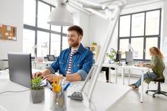 Uśmiechnięty kreatywnie mężczyzna z laptopem pracuje przy biurem obraz royalty free
