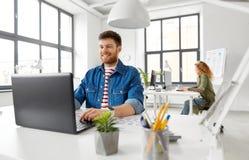 Uśmiechnięty kreatywnie mężczyzna z laptopem pracuje przy biurem fotografia stock