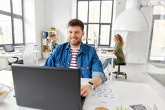 Uśmiechnięty kreatywnie mężczyzna z laptopem pracuje przy biurem obrazy royalty free