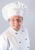 Uśmiechnięty kucbarski szef kuchni na bielu Zdjęcie Royalty Free
