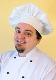 Uśmiechnięty kucbarski szef kuchni na kolorze żółtym Zdjęcia Stock