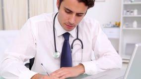 Uśmiechnięty lekarza praktykującego writing na jego schowku zbiory wideo