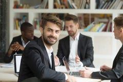 Uśmiechnięty lider zespołu patrzeje kamerę na grupowym korporacyjnym spotkaniu zdjęcie stock