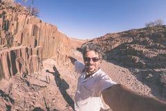 Uśmiechnięty mężczyzna bierze selfie przy powulkaniczną rockową formacją znać jak Zdjęcia Royalty Free