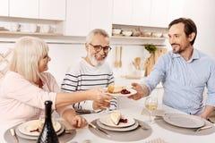 Uśmiechnięty mężczyzna cieszy się rodzinnego gościa restauracji w domu Zdjęcia Stock