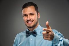 Uśmiechnięty mężczyzna gestykuluje z ręką, wskazuje palec przy kamerą Obraz Stock