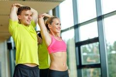 Uśmiechnięty mężczyzna i kobieta ćwiczy w gym Zdjęcia Royalty Free
