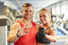 Uśmiechnięty mężczyzna i kobieta pokazuje ok rękę podpisujemy wewnątrz gym Fotografia Stock