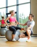 Uśmiechnięty mężczyzna i kobieta z ćwiczenie piłką w gym Zdjęcie Royalty Free