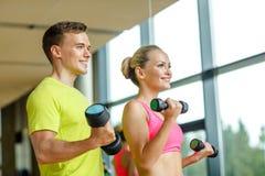 Uśmiechnięty mężczyzna i kobieta z dumbbells w gym Zdjęcia Royalty Free