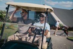 Uśmiechnięty mężczyzna jedzie golfową furę z przyjacielem siedzi blisko obok Obraz Royalty Free