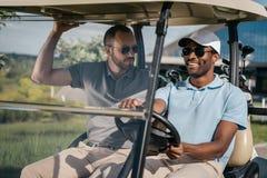 Uśmiechnięty mężczyzna jedzie golfową furę z przyjacielem siedzi blisko obok Zdjęcia Stock