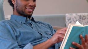 Uśmiechnięty mężczyzna lying on the beach na leżance czyta książkę zbiory