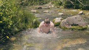 Uśmiechnięty mężczyzna maczanie, kąpanie w zimnej wodzie rzecznej przy letnim dniem i swobodny ruch zbiory wideo