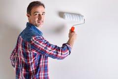Uśmiechnięty mężczyzna maluje ścianę jego dom w bielu obraz stock