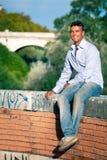 uśmiechnięty mężczyzna miasteczko Siedzący czekanie na depresji ścianie fotografia stock