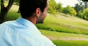 Uśmiechnięty mężczyzna obsiadanie na ławce w parku zbiory