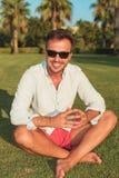 Uśmiechnięty mężczyzna obsiadanie w ogrodowym mieniu jego palmy wpólnie zdjęcia royalty free