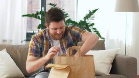 Uśmiechnięty mężczyzna odpakowywa takeaway jedzenie w domu zdjęcie wideo