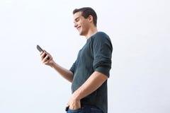 Uśmiechnięty mężczyzna odprowadzenie i patrzeć telefon komórkowego fotografia stock