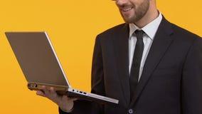 Uśmiechnięty mężczyzna pokazuje aprobaty trzyma laptop, dobra strategia biznesowa, w górę zdjęcie wideo