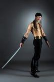 Uśmiechnięty mężczyzna pozuje w pirata kostiumu z saber Obrazy Royalty Free