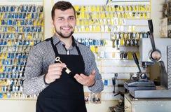 Uśmiechnięty mężczyzna pracownika seansu klucz w warsztacie Zdjęcie Stock