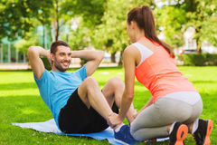 Uśmiechnięty mężczyzna robi ćwiczeniom na macie outdoors Obrazy Stock