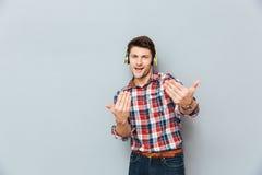 Uśmiechnięty mężczyzna słucha muzyka i pyta ciebie dla tana obraz stock