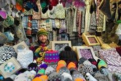 Uśmiechnięty mężczyzna sprzedawanie ciepły odziewa przy Ryskim boże narodzenie rynkiem Zdjęcia Royalty Free