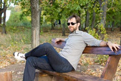Uśmiechnięty mężczyzna target952_0_ na parkowej ławce Zdjęcie Royalty Free
