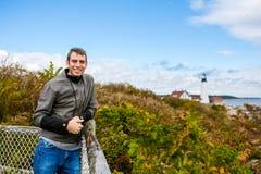 Uśmiechnięty mężczyzna turysta Przy tłem Portlandzka reflektor latarnia morska obraz stock
