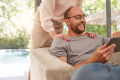 Uśmiechnięty mężczyzna używa cyfrową pastylkę w domu zdjęcia stock