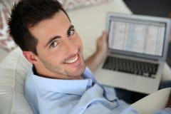 Uśmiechnięty mężczyzna używa laptop Zdjęcia Royalty Free
