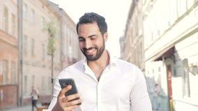 Uśmiechnięty mężczyzna używa telefon komórkowego i odprowadzenie wzdłuż miasto ulicy zbiory