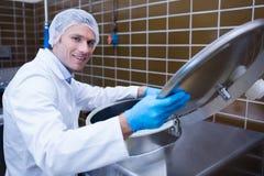 Uśmiechnięty mężczyzna w lab żakiecie otwiera dekiel maszyna obraz stock