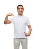 Uśmiechnięty mężczyzna wskazuje palce na on w koszulce obraz stock