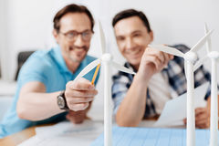 Uśmiechnięty mężczyzna wskazuje przy silnika wiatrowego modelem z ołówkiem Zdjęcia Royalty Free