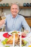 Uśmiechnięty mężczyzna wznosi toast przy boże narodzenie gościem restauracji Fotografia Stock