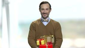 Uśmiechnięty mężczyzna z łęku krawata mienia prezenta pudełkami zbiory wideo