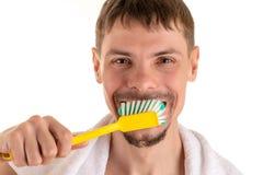 Uśmiechnięty mężczyzna z dużym żółtym toothbrush w ręce i białym ręcznikiem na jego brać na swoje barki Obrazy Stock