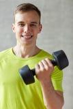 Uśmiechnięty mężczyzna z dumbbell w gym Obraz Stock