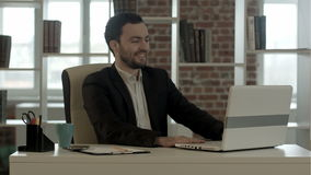 Uśmiechnięty mężczyzna z laptopem w biurze zdjęcie wideo