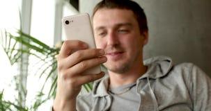 Uśmiechnięty mężczyzna z smartphone w ręce zbiory wideo
