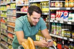 Uśmiechnięty mężczyzna zakupu jedzenie i używać jego smartphone Obrazy Royalty Free