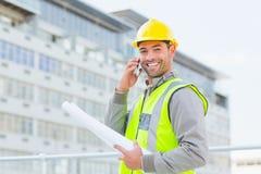 Uśmiechnięty męski architekt opowiada na telefonie komórkowym z projektami Zdjęcia Stock