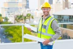Uśmiechnięty męski architekt z projektami i schowkiem Obraz Royalty Free