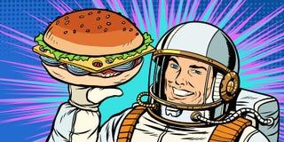 Uśmiechnięty męski astronauta przedstawia hamburger Zdjęcie Royalty Free