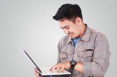 Uśmiechnięty Męski Azjatycki uczeń Pisać na maszynie na laptopie Obrazy Stock
